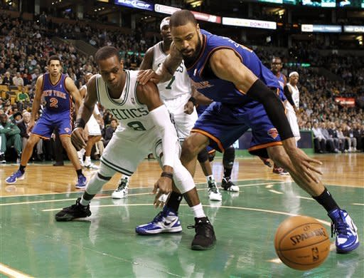 Boston Celtics point guard Rajon Rondo (9) and New York Knicks' Tyson Chandler eye a loose ball during the first quarter of an NBA basketball game in Boston on Friday, Feb. 3, 2012. (AP Photo/Winslow Townson)