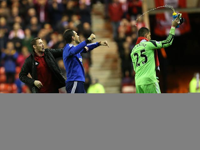 Sunderland's manager Gus Poyet, center, celebrates with goalkeeper Vito Mannone, right, after defeating West Bromwich Albion at the end of their English Premier League soccer match at the Stadium of Light, Sunderland, England, Wednesday, May 7, 2014. (AP Photo/Scott Heppell)