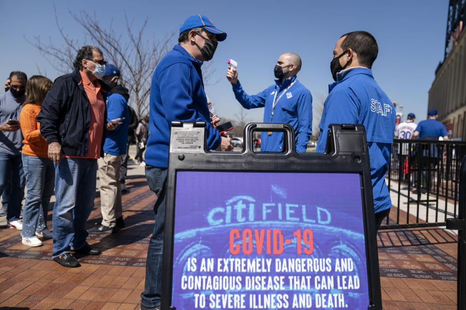 Fans arrive for COVID-19 screenings before entering Citifield before New York Mets home opening baseball game against the Miami Marlins, Thursday, April 8, 2021, in New York. (AP Photo/John Minchillo)