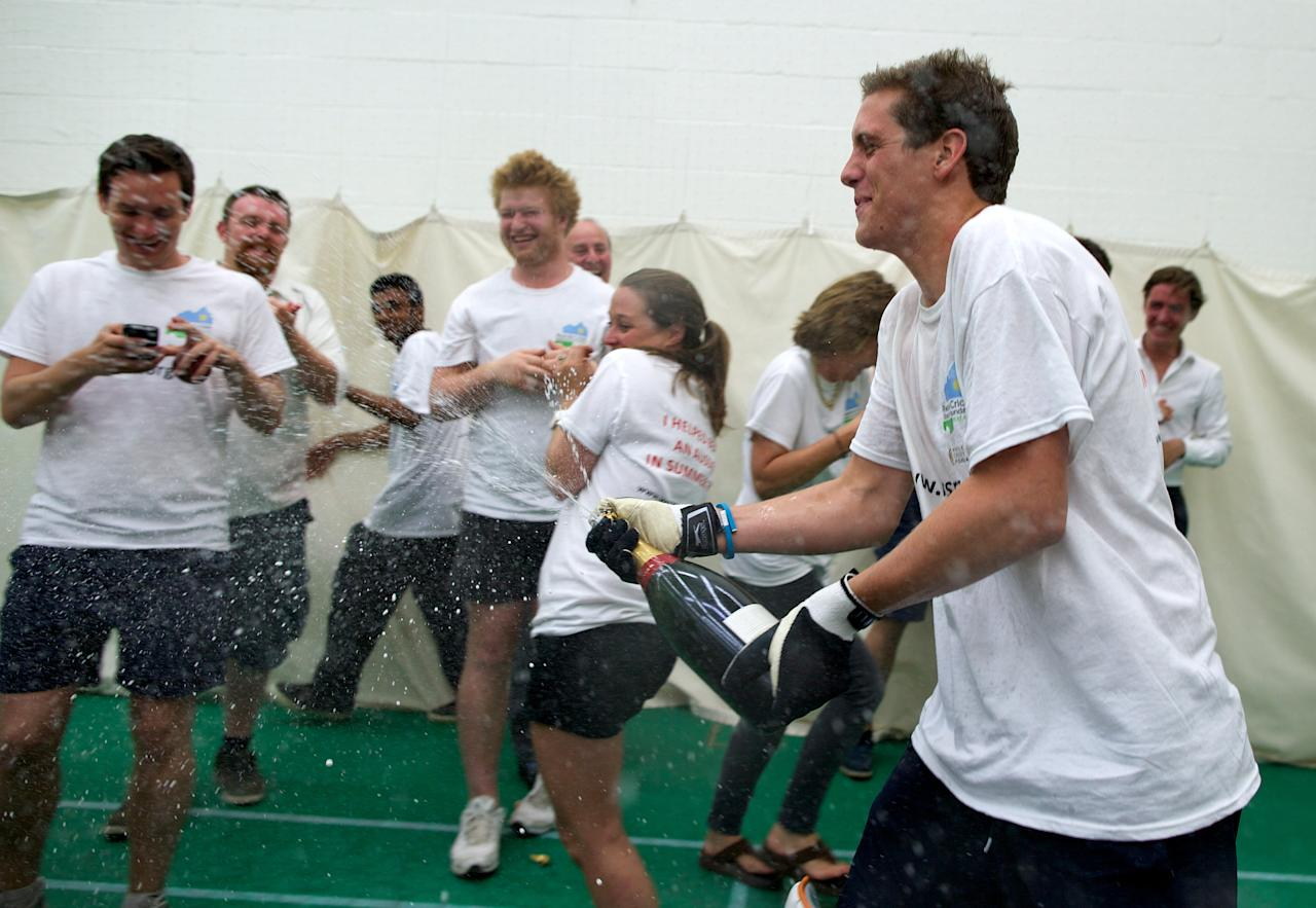 Alby Shale (R) celebrates with family and friends after batting for 26 hours at the Oval cricket club in London, on July 16, 2013. A British graduate collapsed in a heap on Tuesday at The Oval cricket ground in London after batting for 26 hours in a bid to break the world record. The attempt was in aid of the Rwanda Cricket Stadium Foundation -- a charity set up to build the first proper cricket ground in the African country. AFP PHOTO / ANDREW COWIE