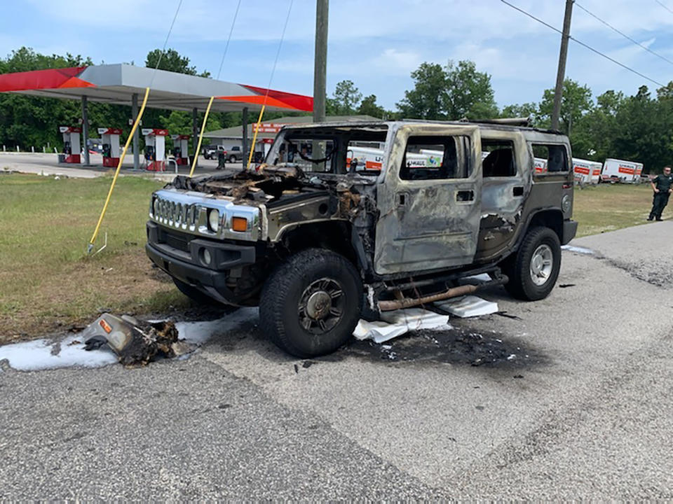 In this photo provided by Citrus County Fire Rescue an officer stands near a Hummer which was destroyed by fire shortly after the driver had filled up four 5-gallon (18-liter) gas containers on Wednesday, May 12, 2021, in Homosassa, Fla. Many authorities are warning of the dangers of hoarding gas as shortages at the pumps are spreading from the South to the Mid-Atlantic states, following a cyberattack that forced a shutdown of the nation's largest gasoline pipeline. (Citrus County Fire Rescue via AP)