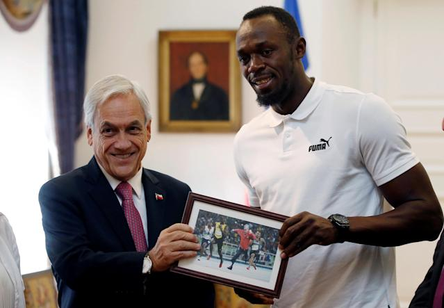 Former sprinter Usain Bolt poses next to the Chilean President Sebastian Pinera, showing a photomontage of the President Pinera running next to him, during his visit at the government palace in Santiago, Chile April 1, 2019. REUTERS/Rodrigo Garrido