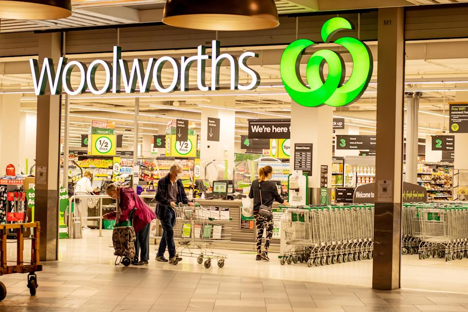 Customers walk out of the front of a Woolworths store with trolleys.