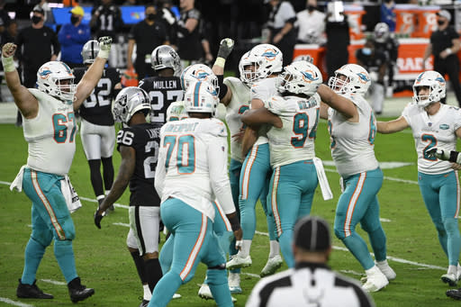Miami Dolphins players celebrate after kicker Jason Sanders (7) made a game-winning field goal with seconds left during the second half of an NFL football game against the Las Vegas Raiders, Saturday, Dec. 26, 2020, in Las Vegas. (AP Photo/David Becker)