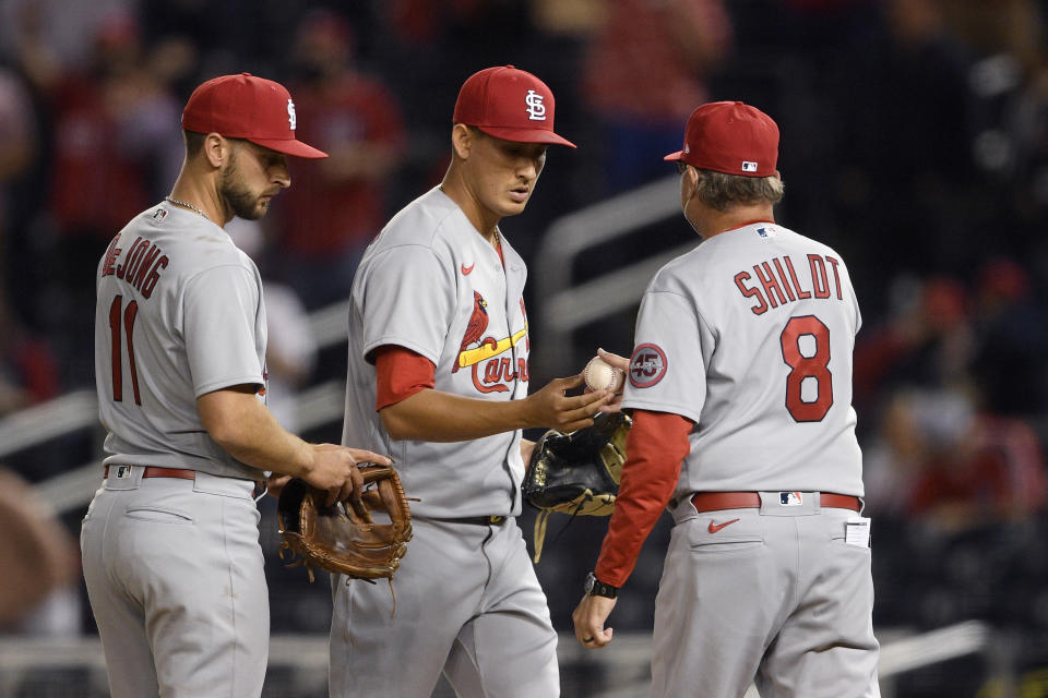 St. Louis Cardinals relief pitcher Giovanny Gallegos, center, is pulled from the baseball game by manager Mike Shildt (8) during the eighth inning against the Washington Nationals, Tuesday, April 20, 2021, in Washington. At left is Cardinals shortstop Paul DeJong. (AP Photo/Nick Wass)