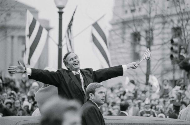 PHOTO: Vice President George Bush waves a small U.S. flag as he and his wife, Barbara, ride in the inaugural parade January 20. He was responding to applause from people lining the parade route, Jan. 20, 1981. (Bettmann Archive/Getty Images, file)
