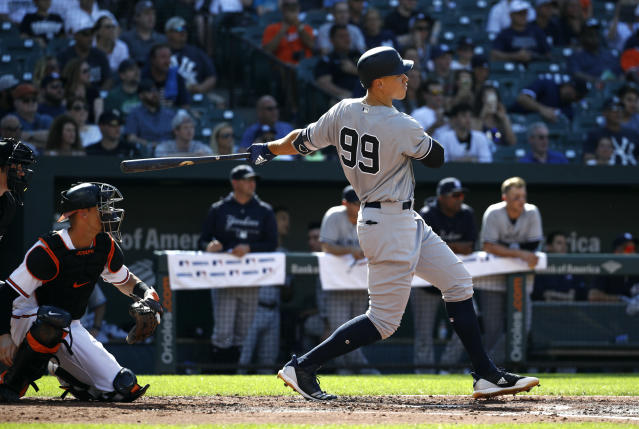 New York Yankees' Aaron Judge singles in front of Baltimore Orioles catcher Caleb Joseph and home plate umpire John Tumpane in the third inning of the first baseball game of a doubleheader, Monday, July 9, 2018, in Baltimore. Tyler Wade scored on the play. (AP Photo/Patrick Semansky)