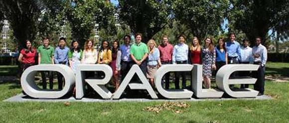 Picture of several Oracle employees standing outside behind its logo.