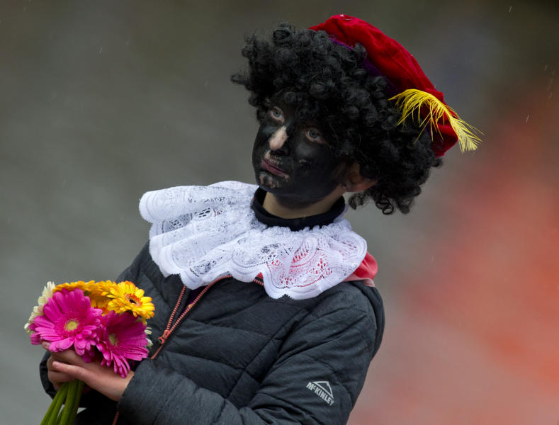 "In this Saturday, Nov. 18, 2017, file photo, a child dressed as Black Pete waits for the arrival of Sinterklaas, in Dokkum, northern Netherlands. A court in the Netherlands has convicted 34 people on Friday NOv. 9, 2018, who blocked a highway last year to prevent anti-racism demonstrators reaching the nationally televised arrival of Sinterklaas, the Dutch version of Santa Claus, and his helpers called ""Zwarte Piet"", or Black Petes. Black Pete is often played by white people with their faces daubed in dark makeup. (AP Photo/Peter Dejong)"
