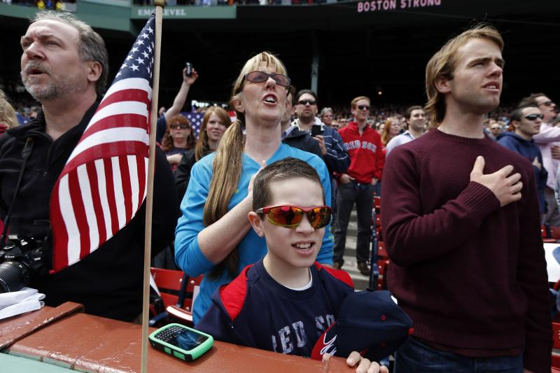 Fans, accompanied by the stadium organist, sing the national anthem before a baseball game between the Boston Red Sox and the Kansas City Royals in Boston, Saturday, April 20, 2013. (AP Photo/Michael Dwyer)