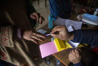 A local poling officer applies indelible ink mark on the finger of a Kashmiri casting her votes during the first phase of District Development Councils election on the outskirts of Srinagar, Indian controlled Kashmir, Saturday, Nov. 28, 2020. Thousands of people in Indian-controlled Kashmir voted Saturday amid tight security and freezing cold temperatures in the first phase of local elections, the first since New Delhi revoked the disputed region's semiautonomous status. (AP Photo/Mukhtar Khan)