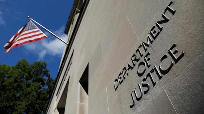 The Department of Justice symbol is seen on a wall beneath a flying American flag in this low-angle shot