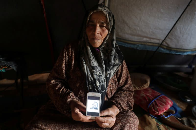 Jouriya Ali, 74, displays picture of her deceased son in Idlib