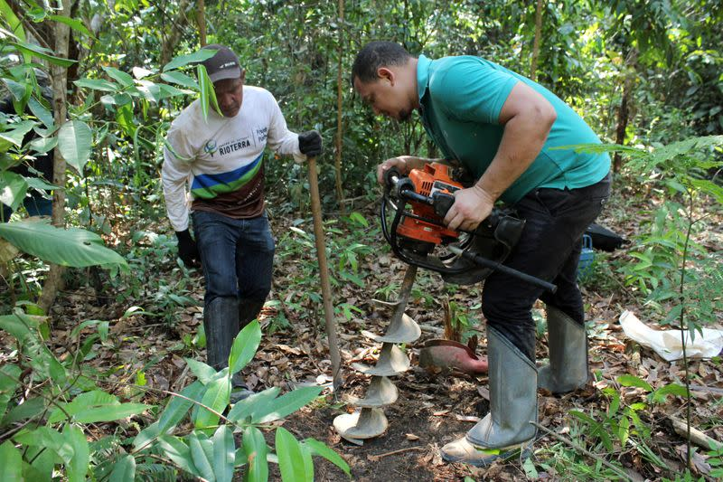 Agronomy engineer Ueliton Pinheiro Januario and Rioterra plant nursery worker Juciney Pinheiro dos Santos dig for soil samples while measuring carbon content on a parcel of Amazon rainforest in Itapua do Oeste