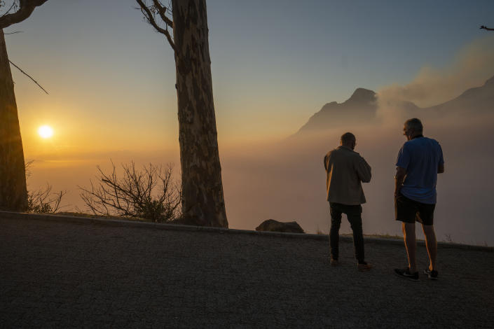 Capetonians watch the sun rise from the top of Signal Hill as smoke engulfs the city of Cape Town, South Africa, Tuesday, April 20, 2021. A massive fire spreading on the slopes of the city's famed Table Mountain, at right, is kept under control as firemen and helicopters take advantage of the low winds to contain the blaze. (AP Photo/Jerome Delay)