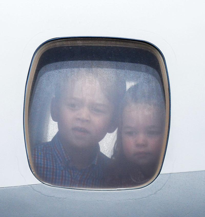Princess Charlotte of Cambridge and Prince George of Cambridge look out of the window of the plane as they arrive at Warsaw airport during an official visit to Poland. Prince George wears a blue and red checked button down shirt for his arrival in Europe.