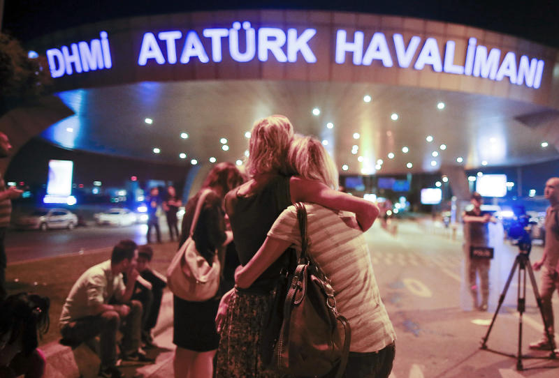 Passengers embrace each other at the entrance to Istanbul's Ataturk airport, early on June 29, 2016 following their evacuation after a blast. (Photo: Emrah Gurel/AP)
