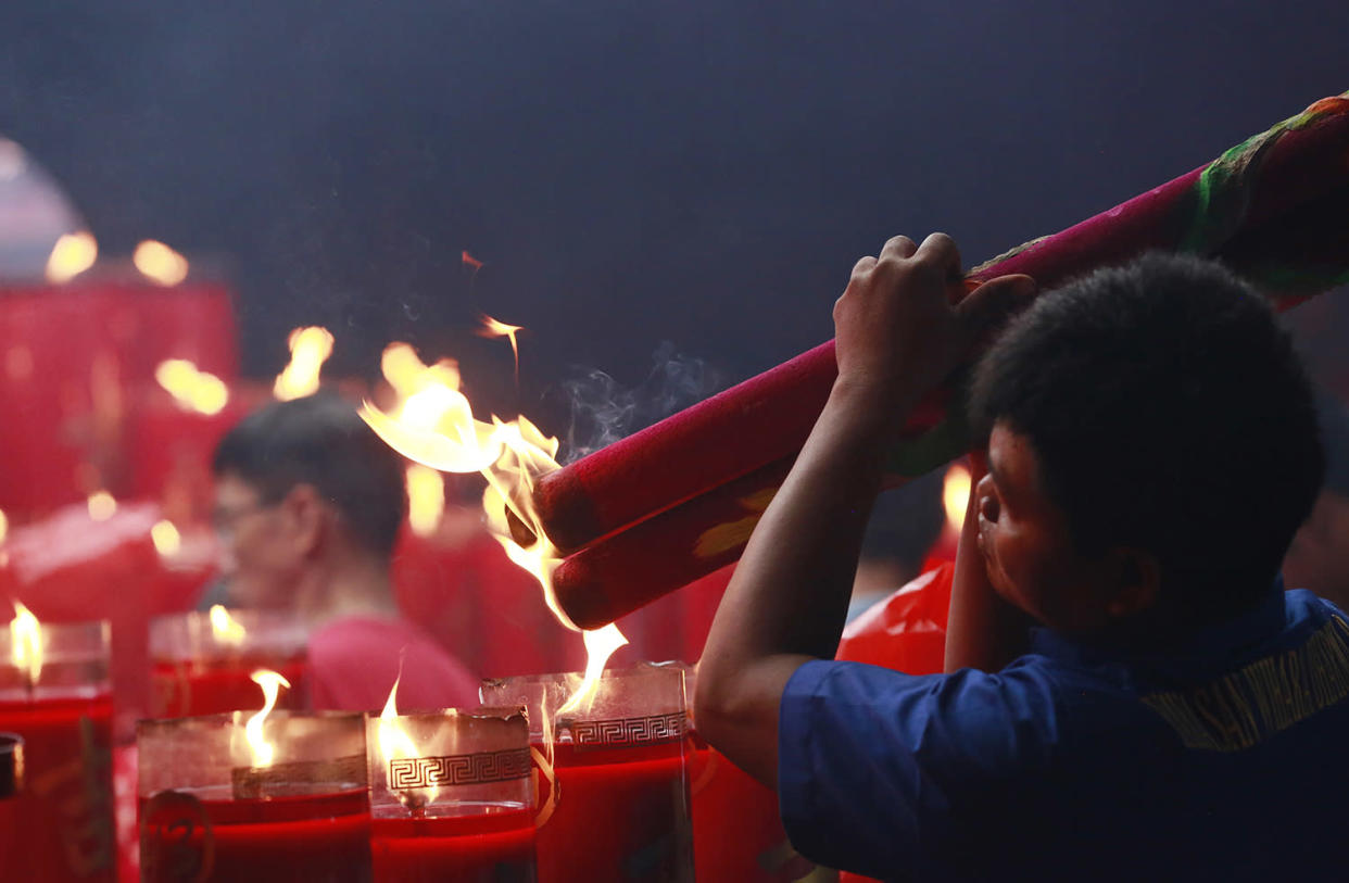 An ethnic Chinese man lights incense sticks during celebrations of the Lunar New Year at the Dharma Bakti Temple in Jakarta, Indonesia, Saturday, Jan. 28, 2017. Ethnic Chinese in the world's most populous Muslim country are celebrating the Year of the Rooster. (AP Photo/Achmad Ibrahim)