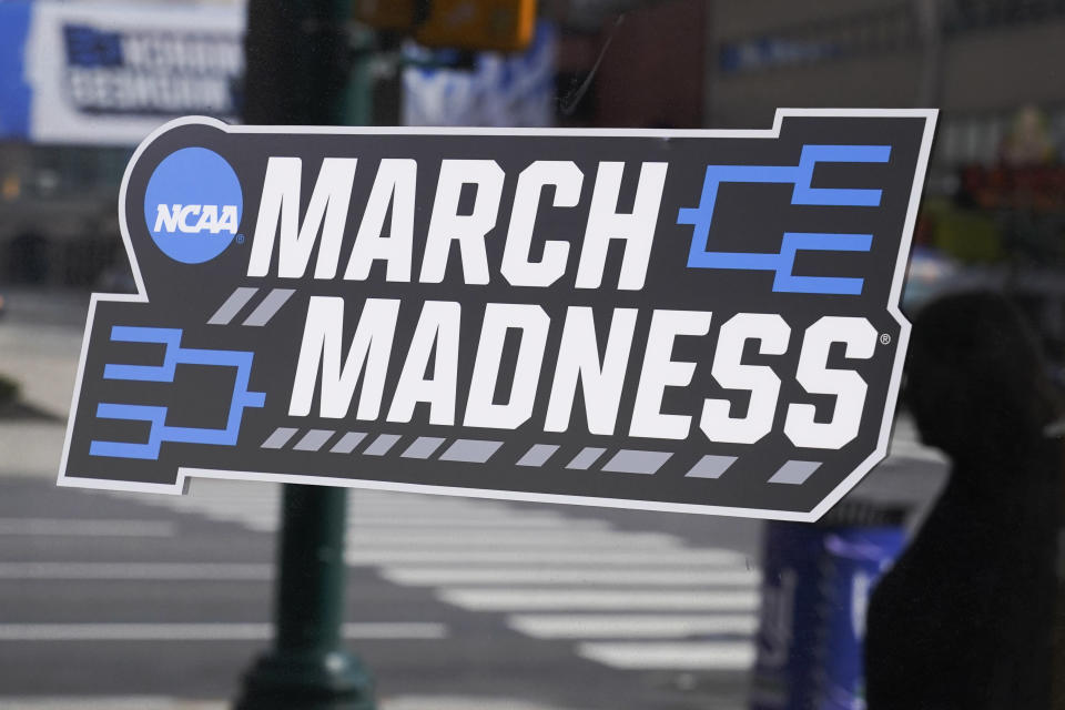 A March Madness sticker for the NCAA college basketball tournament is placed on a window in downtown Indianapolis, Wednesday, March 17, 2021. (AP Photo/Darron Cummings)