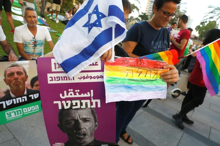 "Members of the LGBT community hold a banner reading in Hebrew ""A homophobic racist has to quit"" during a rally against Israel's Education Minister Rafi Peretz following his remarks on gay conversion therapy in the Israeli coastal city of Tel Aviv (AFP Photo/JACK GUEZ)"