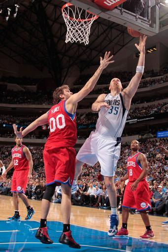 DALLAS, TX - DECEMBER 18: Chris Kaman #35 of the Dallas Mavericks shoots a layup against Spencer Hawes #00 of the Philadelphia 76ers on December 18, 2012 at the American Airlines Center in Dallas, Texas. (Photo by Danny Bollinger/NBAE via Getty Images)
