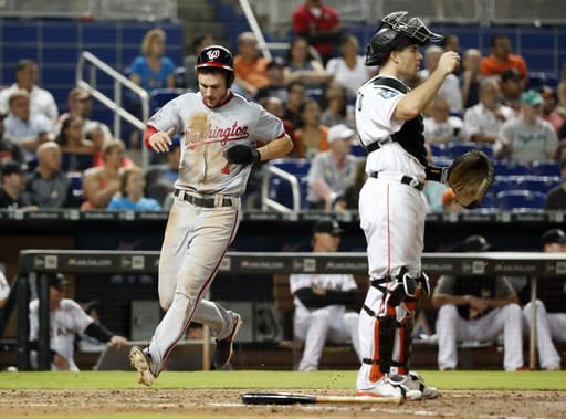 Washington Nationals' Trea Turner (7) scores on a single by Anthony Rendon as Miami Marlins catcher J.T. Realmuto waits for the throw during the sixth inning of a baseball game, Tuesday, Sept. 18, 2018, in Miami. (AP Photo/Wilfredo Lee)