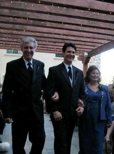 Michael Rudometkin walks arm-in-arm with his parents, Gary and Rose, at his wedding in 2010.