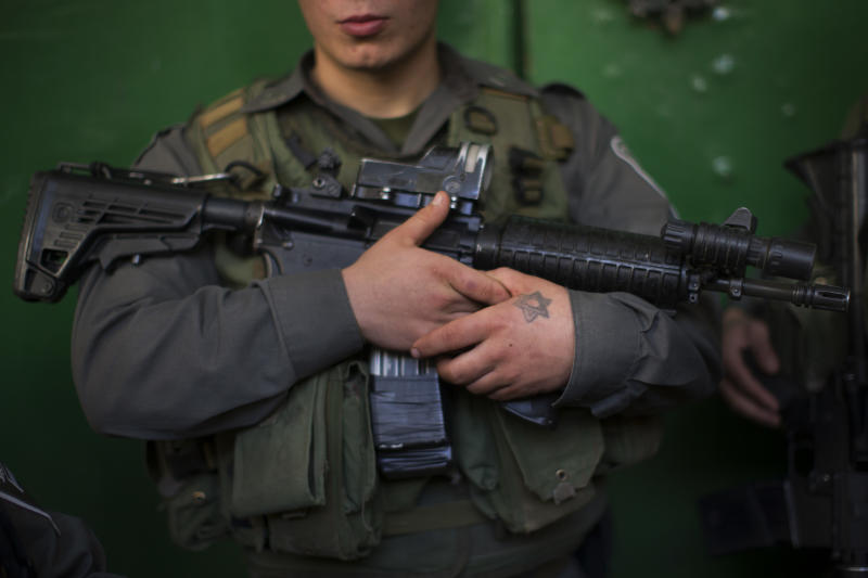 An Israeli border police guards a door inside the site known to Jews as the Tomb of the Patriarchs, and to Muslims as the Ibrahimi Mosque, in the West Bank city of Hebron, Monday, Jan. 14, 2013. (AP Photo/Bernat Armangue)