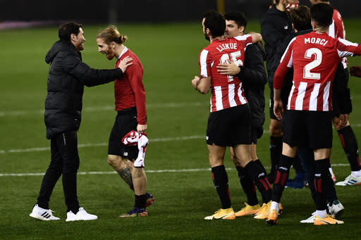 Athletic Bilbao's head coach Marcelino, left, celebrates with Iker Muniain, second left, and teammates at the end of the Spanish Super Cup semi final soccer match between Real Madrid and Athletic Bilbao at La Rosaleda stadium in Malaga, Spain, Thursday, Jan. 14, 2021. Athletic Bilbao won 2-1 and will play the final. (AP Photo/Jose Breton)