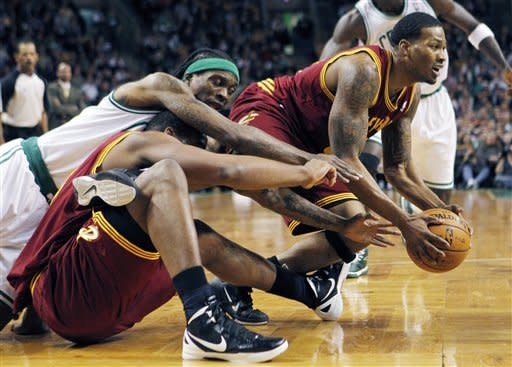 Boston Celtics' Marquis Daniels, top left, scrambles for the ball with Cleveland Cavaliers' Samardo Samuels, bottom left, and Alonzo Gee, right, in the second quarter of an NBA basketball game in Boston, Sunday, Jan. 29, 2012. (AP Photo/Michael Dwyer)