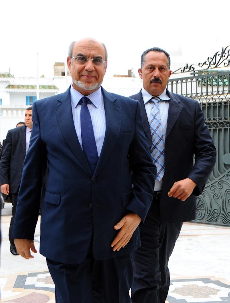 Tunisian Prime Minister Hamadi Jebali,  arrives, followed by a body guard, for a meeting with representatives of all Tunisian political parties, to see if there is sufficient support for his solution to end the country's ongoing political crisis in Carthage, outside Tunis, Monday, Feb. 18, 2013.  Jebali's initiative, while supported by the opposition, puts him on a collision course with the moderate Islamist Ennahda Party, which dominates the government. (AP Photo/Hassene Dridi)
