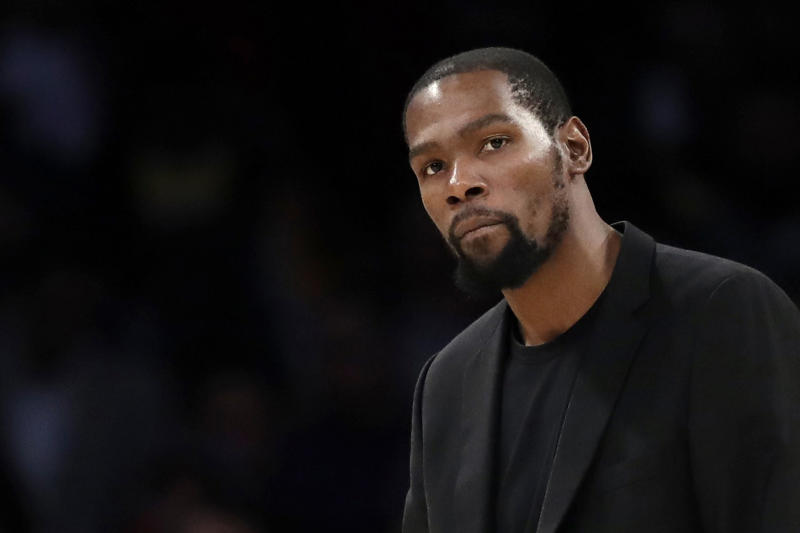 FILE- In this March 10, 2020, file photo, Brooklyn Nets' Kevin Durant watches during the second half of the team's NBA basketball game against the Los Angeles Lakers in Los Angeles. Durant is among the four Brooklyn Nets who have tested positive for the new coronavirus. A backlash roiled across social media Wednesday, March 18, as several celebrities and professional athletes revealed that they had been tested for the coronavirus, even when they didn't have a fever or other tell-tale symptoms. (AP Photo/Marcio Jose Sanchez, file)