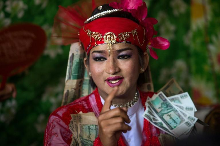 A medium wearing a red outfit and heavy make-up prepares to dance in honour of Myanmar's spirit guardian of drunkards and gamblers