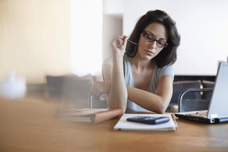 Woman holding a pen and looking at financial paperwork.