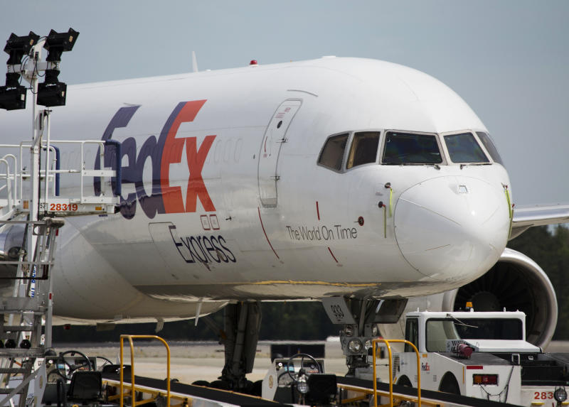 FILE- In this April 18, 2017, file photo, a FedEx cargo plane sits idle during the day at Richmond International Airport in Sandston, Va. FedEx says one of its pilots was detained in China after an item was found in his luggage before he boarded a commercial flight. The company said Thursday, Sept. 19, 2019 the pilot was later released, and it is working with Chinese authorities to understand what happened at the airport in Guangzhou, in southern China.(AP Photo/Steve Helber, File)