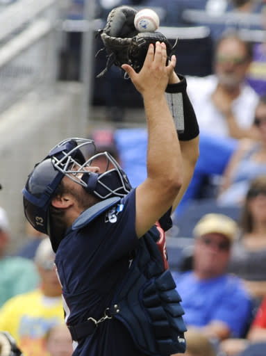 Mississippi catcher Austin Knight catches a foul ball hit by Virginia's Joe McCarthy (31) in the fifth inning of an NCAA College World Series baseball game in Omaha, Neb., Saturday, June 21, 2014. (AP Photo/Eric Francis)