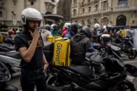 Delivery workers gather during a protest in front of the Spanish Parliament in Madrid, Spain, Tuesday, May 11, 2021. Spain has approved a pioneering law that gives delivery platforms a mid-August deadline to hire the workers currently freelancing for them and that requires transparency of artificial intelligence to manage workforces. (AP Photo/Manu Fernandez)