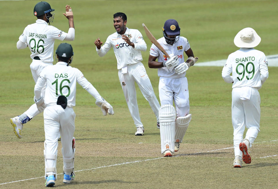 Bangladesh's Mehidy Hasan, center, celebrates with teammates the dismissal of Sri Lanka's Oshada Fernando, second right, during the second day of the second test cricket match between Sri Lanka and Bangladesh in Pallekele, Sri Lanka, Friday, April 30, 2021. ( AP Photo/Sameera Peiris)