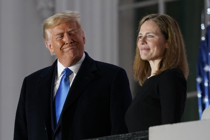FILE - In this Monday, Oct. 26, 2020 file photo, President Donald Trump and Amy Coney Barrett stand on the Blue Room Balcony after Supreme Court Justice Clarence Thomas administered the Constitutional Oath to her on the South Lawn of the White House White House in Washington. President Donald Trump's deep imprint on the federal courts is a rare point of agreement about the president across the political spectrum. With a major assist from Senate Majority Leader Mitch McConnell, Trump and his White House staff relentlessly, almost robotically, filled nearly every opening in the federal judiciary, undeterred by Democratic criticism. (AP Photo/Patrick Semansky, File)