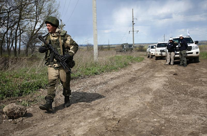 An armed pro-Russian separatist of the self-proclaimed Lugansk People's Republic walks past a convoy of the OSCE near Lugansk, on April 25, 2017 (AFP Photo/Aleksey FILIPPOV)