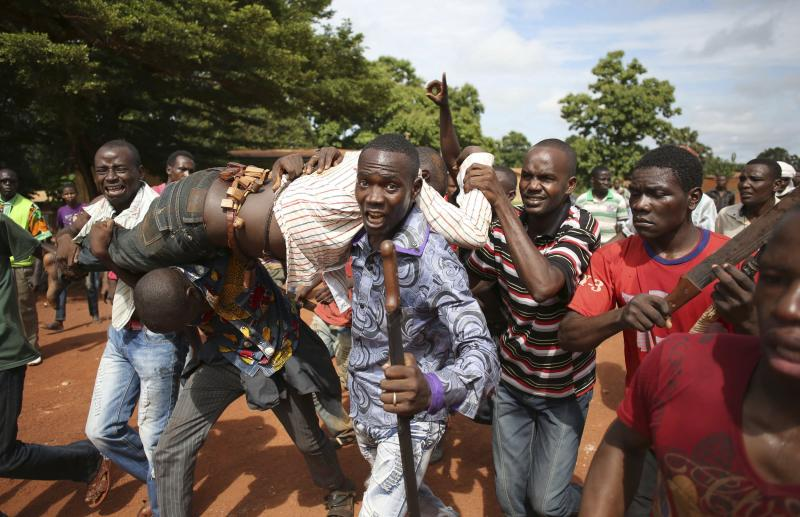 Protesters carry a man who was shot by French soldiers after French troops opened fire at protesters blocking a road in Bambari