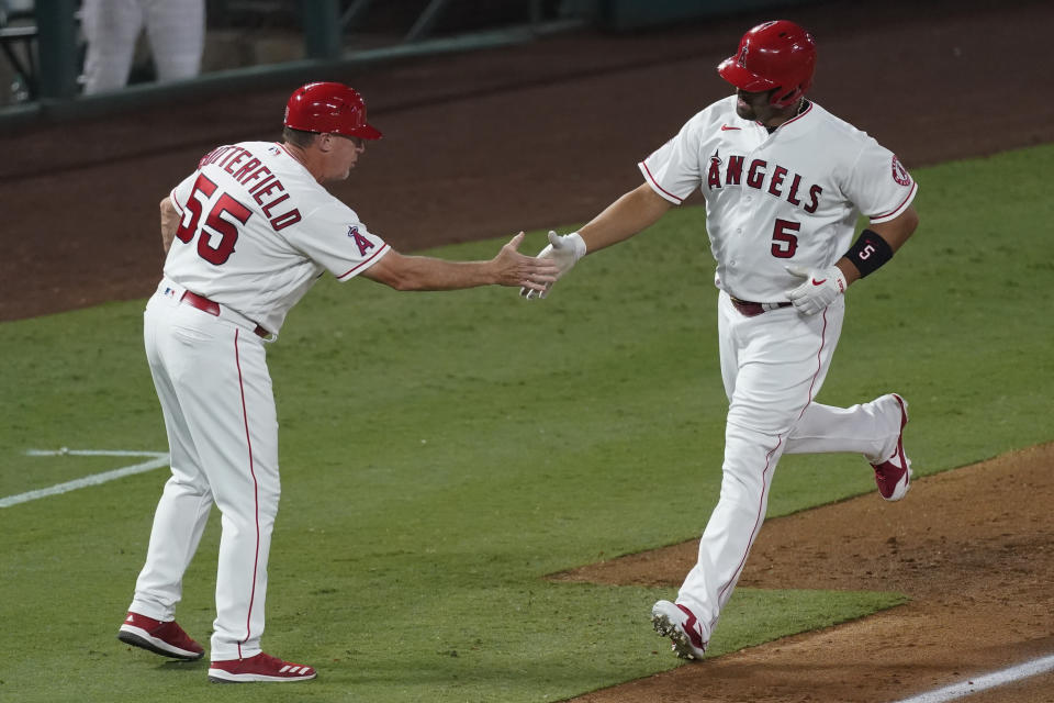 Los Angeles Angels' Albert Pujols, right, is greeted by third base coach Brian Butterfield as he runs the bases on a solo home run during the fifth inning of the team's baseball game against the Texas Rangers on Friday, Sept. 18, 2020, in Anaheim, Calif. (AP Photo/Ashley Landis)