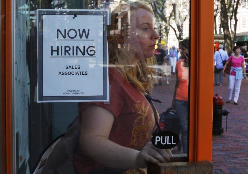"A woman past a ""Now Hiring"" sign as she leaves the Urban Outfitters store at Quincy Market in Boston"