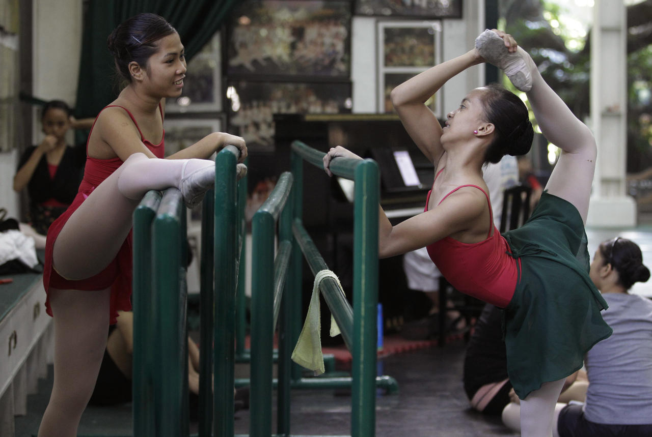 In this photo taken Nov. 25, 2012, Filipino slum dweller Jessa Balote, right, talks with another student as she stretches before the start of classes at Ballet Manila in the Philippine capital. Balote, who used to tag along with her family as they collect garbage at a nearby dumpsite, is a scholar at Ballet Manila's dance program. As an apprentice, she makes around 7,000 pesos ($170) a month, sometimes double that, from stipend and performance fees. (AP Photo/Aaron Favila)