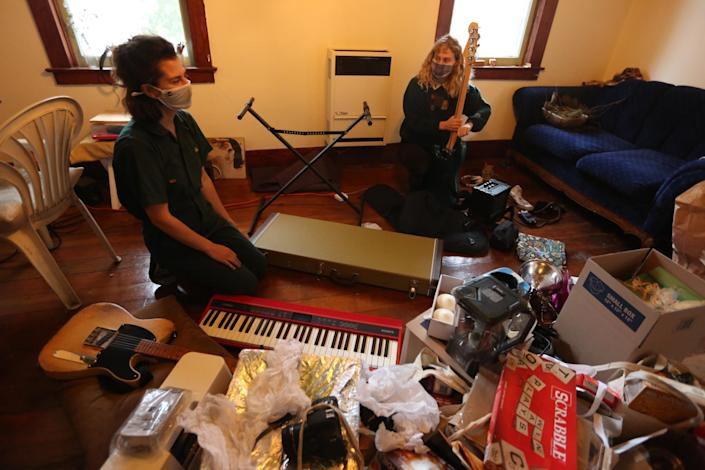 Musicians Georgina Hahn, left, and Veronica Lorenzini, both 24, pack up their Echo Park apartment