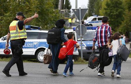 A German policeman directs migrants towards a registration point after crossing the border from Austria in Freilassing, Germany September 17, 2015. REUTERS/Michaela Rehle