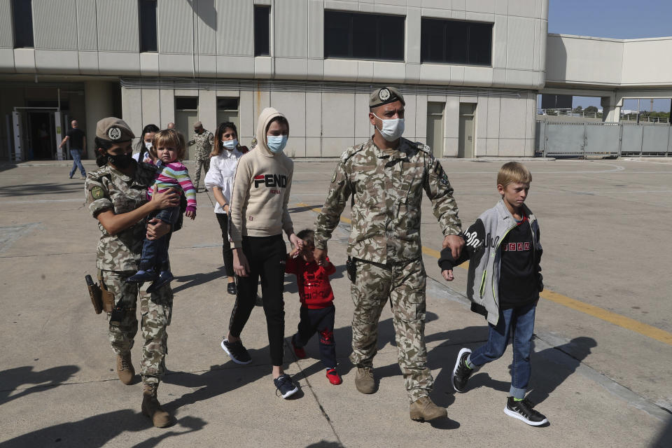 """Members of the Lebanese General Security forces walk with Albanian children during an operation to take them back home to Albania from al-Hol, northern Syria, at the Rafik Hariri International Airport in Beirut, Lebanon, Tuesday, Oct. 27, 2020. The repatriation of four children and a woman related to Albanian nationals who joined Islamic extremist groups in Syria """"is a great step"""" to be followed by more repatriations, Albania's prime minister said Tuesday in Beirut. (AP Photo/Bilal Hussein)"""