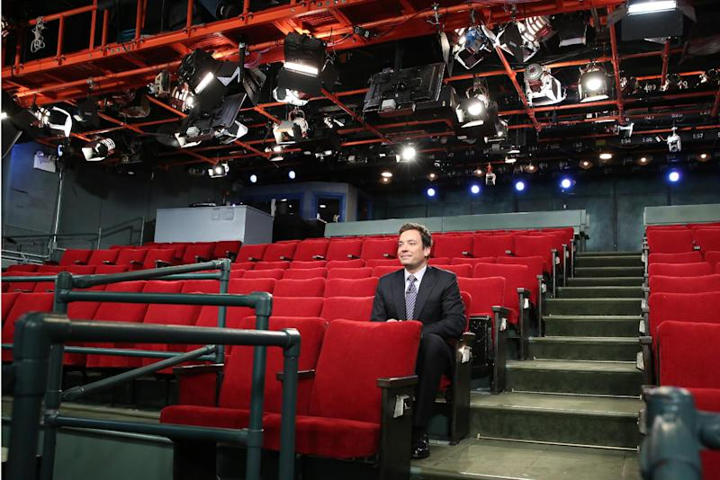 """This Monday, Oct. 29, 2012 photo released by NBC shows host Jimmy Fallon sitting in an empty studio where his show """"Late Night with Jimmy Fallon,"""" is taped in New York. The audience was absent due to inclement weather caused by superstorm Sandy. (AP Photo/NBC, Lloyd Bishop)"""