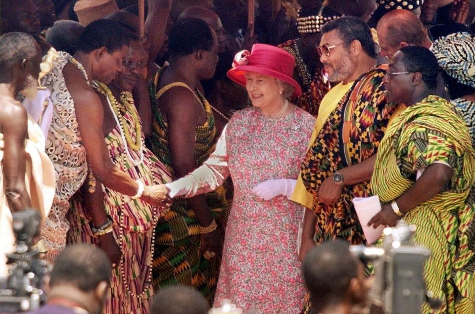 FILE - In this Monday, Nov. 8, 1999 file photo, Britain's Queen Elizabeth II, flanked to the right by Ghanaian President Jerry Rawlings, shakes hands with one of over a dozen Ghanaian tribal chiefs lined up to greet her, at an outdoor ceremony in Accra, Ghana. Ghana's former president Jerry Rawlings, who staged two coups and later led the West African country's transition to a stable democracy, has died aged 73, according to the state's Radio Ghana and the president Thursday, Nov. 12, 2020. (AP Photo/Brennan Linsley, File)