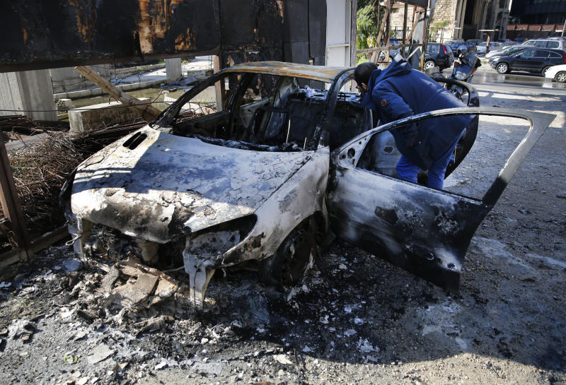 A man looks at a burned car that was set on fire early Tuesday by supporters of the Shiite Hezbollah and Amal Movement groups, in Beirut, Lebanon, Tuesday, Dec. 17, 2019. Supporters of Lebanon's two main Shiite groups Hezbollah and Amal clashed with security forces and set fires to cars in the capital early Tuesday, apparently angered by a video circulating online that showed a man insulting Shiite figures.(AP Photo/Hussein Malla)